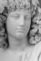 Fragment of a marble statue. Head of a woman with hair and decoration in the form of grape leaves