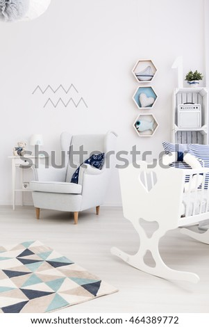 Fragment of a newborn boy's room with cosy armchair and a white cradle with a lifebelt inside #464389772