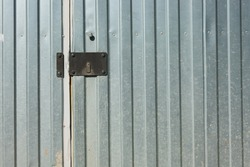Fragment of a silver metal fence with a door. There is a black lock bar with a closed keyhole. Background. Texture.