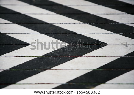 Photo of  Fragment of a striped wrinkled black and white piece of a cloth fabric as a background texture