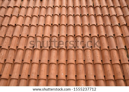 Fragment of a tiled roof. Clay tiles. Background. Pattern. Terracotta. Gray. Ocher. #1555237712
