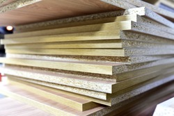 Fragment of a wooden panel made of fiberboard in workshop. Medium Density Fiberboard (MDF). Woodworking industry and furniture assembly concept.