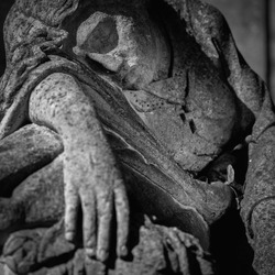 Fragment of an ancient stone statue of sad and desperate woman on tomb as a symbol of death and the end of human life.