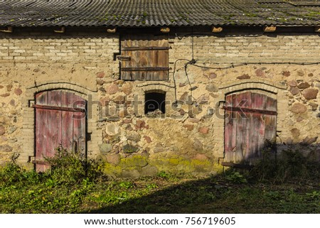 Fragment of an old abandoned stone barn. Walls of untreated stone on clay mortar. Slate roof. Late autumn, sunny day. Podlasie, Poland.