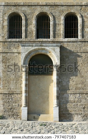 Fragment of an old fortification wall with an arched portal and arched windows. A vintage prison building . Ancient sea port.Yaffo, Israel #797407183
