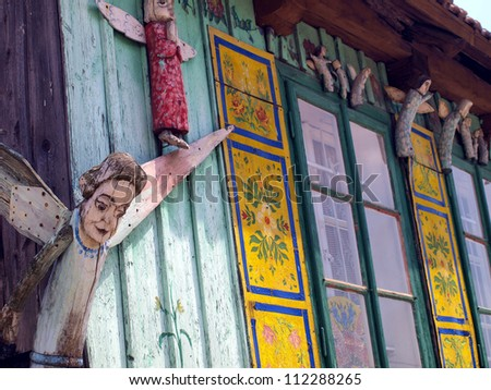 fragment of an old hut in Olsztyn near Czestochowa with one colored wall decorated with sculptures of angels