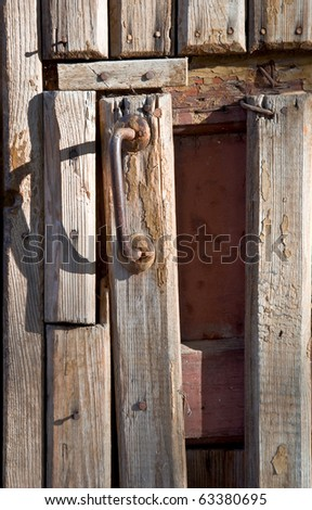 Fragment of an old wooden door with a handle. Close-up, front.