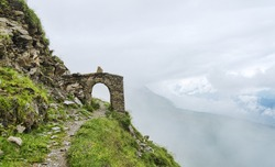 Fragment of ancient building - brick arch among fog and alpine landscape