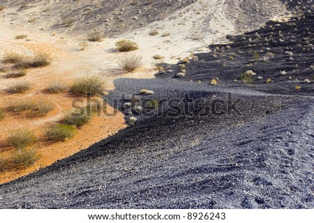 Fragment of black lava and orange clay and salt mineral deposits in geological formations in Ubehebe Volcano, Death Valley National Park