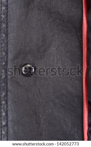Fragment of black leather jacket with button