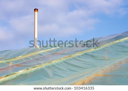 Fragment of film greenhouses with the chimney against the sky