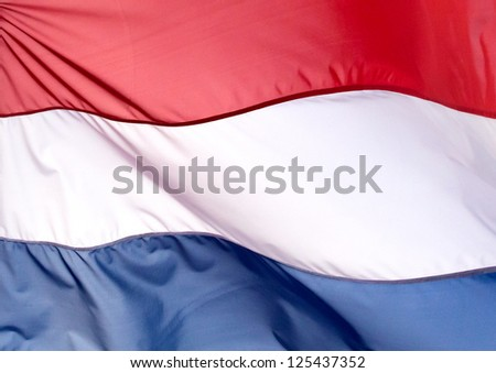 Fragment of flag of the Netherlands against the blue sky - stock photo