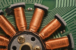 Fragment of floppy drive motor with copper wire coils closeup
