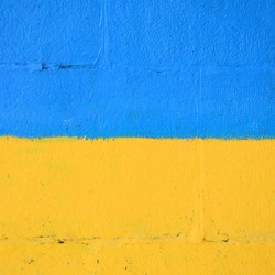 Fragment of graffiti drawings. The old wall decorated with paint stains in the style of street art culture. Ukrainian flag
