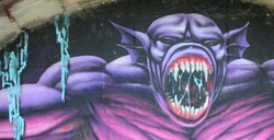 Fragment of graffiti drawings. The old wall decorated with paint stains in the style of street art culture. Purple scary monster