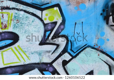 Fragment of graffiti drawings. The old wall decorated with paint stains in the style of street art culture. Colored background texture in cold tones #1260106522