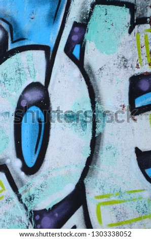 Fragment of graffiti drawings. The old wall decorated with paint stains in the style of street art culture. Colored background texture in cold tones #1303338052