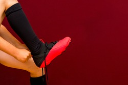fragment of legs Young caucasian soccer kit socks soccer shoes red background.Copy space.