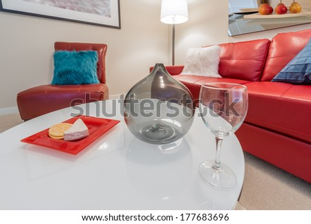 Fragment of luxury brand new living suite. Nicely decorated modern family, living room with decorative vase and vine glass on the coffee table and red color leather couch and chair. Interior design