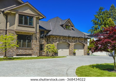 Fragment of luxury house with double garage and concrete driveway in front. Front yard of luxury family house with green lawn and driveway in front on blue sky background #368434022