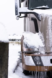 Fragment of modern coffee-colored truck covered with snow and ice
