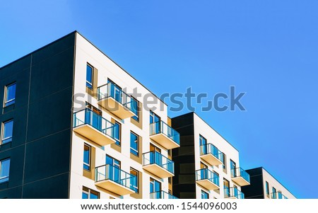 Fragment of Modern residential apartment with flat buildings exterior. Detail of New luxury house and home complex. Part of City Real estate property and condo architecture. Copy space. Blue sky Foto stock ©