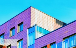 Fragment of Modern residential flat with apartment building exterior. Detail of New luxury house and home complex. Part of City Real estate property and condo architecture. Copy space. Blue sky