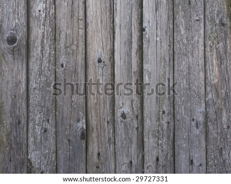 Fragment of old damaged gray wooden fence