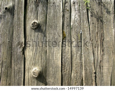 Fragment of old destroyed wooden uncolored fence