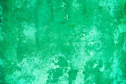 Fragment of old house wall close-up. Green background. Peeling plaster on concrete surface. tinted green. Cracks in paint. Copy space. Place for text. Selective focus image.