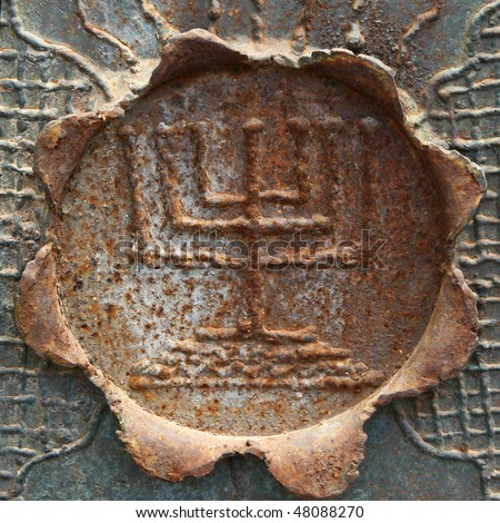Fragment of old Jerusalem fence with decorative menorah on the rusty metal flower.