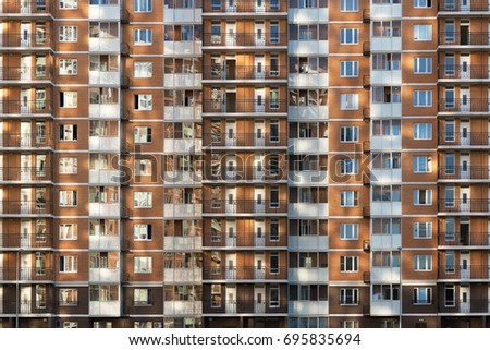 Fragment of one of the serial high-rise apartment buildings in Moscow suburbs with the sunset glare on the wall and windows. New building construction