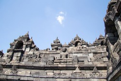 Fragment of one of the stone walls of Borobudur Buddhist temple with bell stupas and Buddhist figures during a sunny day in Indonesia Asia