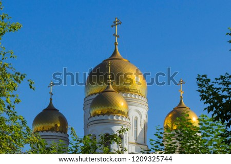 Fragment of orthodox church against the background of the blue sky in an environment of foliage of trees. #1209325744