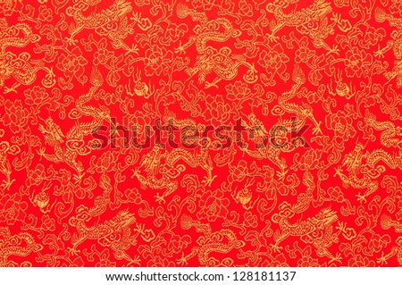 Fragment of red chinese silk with golden dragons and flowers as sign for Chinese New Year celebration.