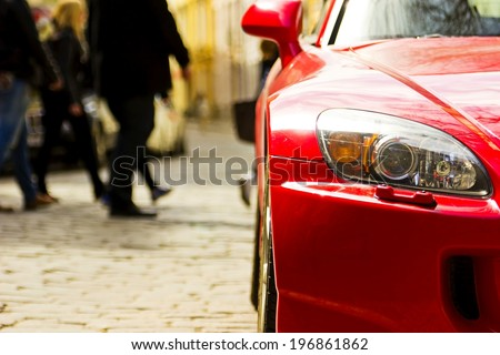 Fragment of red sport car with headlight in sunlight at sunset #196861862