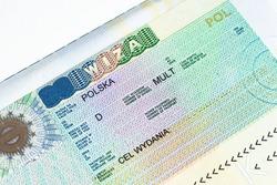Fragment of Schengen multi entrance Polish visa in passport close-up. Travel Polish visa.