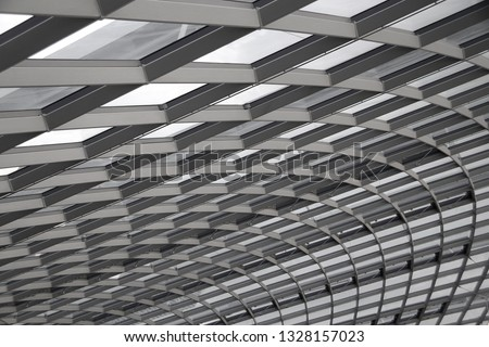 Fragment of structural glazing. Close-up of industrial or office building Glass wall with steel framework. Hi-tech abstract background on the subject of modern architecture, industry or technology.