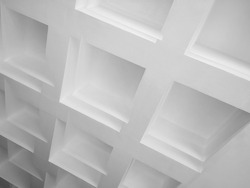 Fragment of structured ceiling. Abstract modern architecture or interior design. Minimalist geometric background in gray halftones. Angular polygonal structure of surfaces and edges.