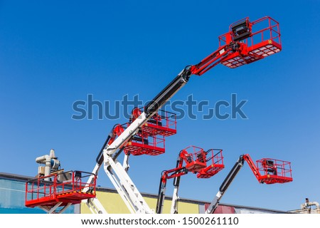 Fragment of the booms with baskets and top parts of different articulated boom lifts and scissor lifts on a background of clear sky