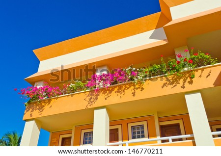 Fragment of the colorful luxury caribbean resort hotel building. Balcony with some flowers.  Bahia Principe, Riviera Maya.