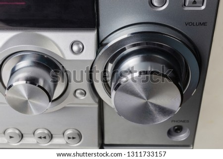 Fragment of the front panel of home stereo mini music system with volume control knob and other control buttons close-up at selective focus