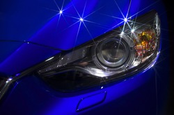 Fragment of the hood and headlights sports blue car with silver stars