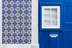 Fragment of the house facade with azulejos decoration, white window and mail box in Lisbon, Portugal.