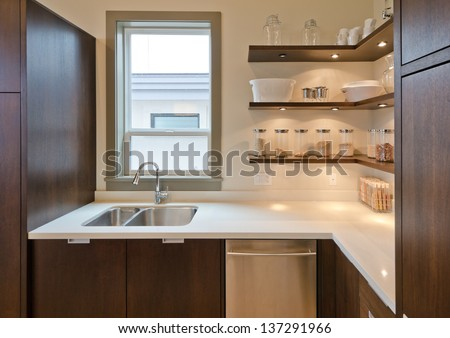 Fragment of the luxury modern kitchen with some shelves with  jars, cans in the corner and window atop of the sink. Interior design.