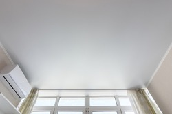 Fragment of the suspended ceiling above the window in the room, next to air conditioning
