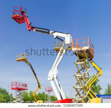 Fragment of top parts different self propelled articulated boom lifts and scissor lifts on background of clear sky