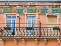 Fragment of traditional Portuguese house, with white plastic windows and ornate metal balcony railings. Old building wall with colorful ceramic tiles. Background from decorative painted Azulejo tiles.