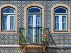Fragment of traditional Portuguese house with white windows and door with ornate metal balcony railings. Old building wall with colorful ceramic tiles. Background from decorative painted Azulejo tiles