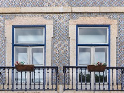 Fragment of traditional Portuguese house, with wooden windows and ornate metal balcony railings. Old building wall with colorful ceramic tiles. Background from decorative painted Azulejo tiles.